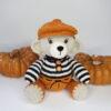 Hækleopskrift på 30 cm høj Bamse med rustfarvede bukser og kasket og stribet trøje